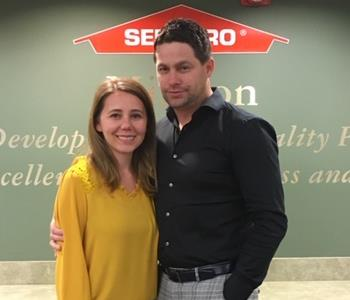 Woman with brown hair and mustard shirt with a man with dark hair and a black shirt standing in front of a SERVPRO sign.
