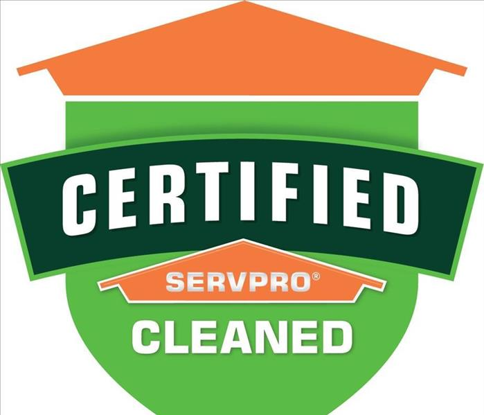 Table tent signs describing the Certified: SERVPRO Cleaned programon top of a wooden table.